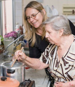 Woman assisting and elderly person with cooking