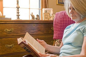 Elderly woman reading a book in her home