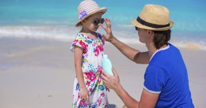 Man putting sunscreen on girl while standing on beach.